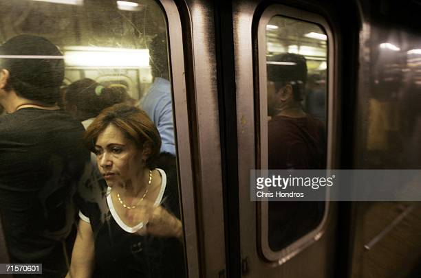 A woman squeezes onto a crowded subway car at the Times Square station August 2 2006 in New York City Forecasters have called for high temperatures...