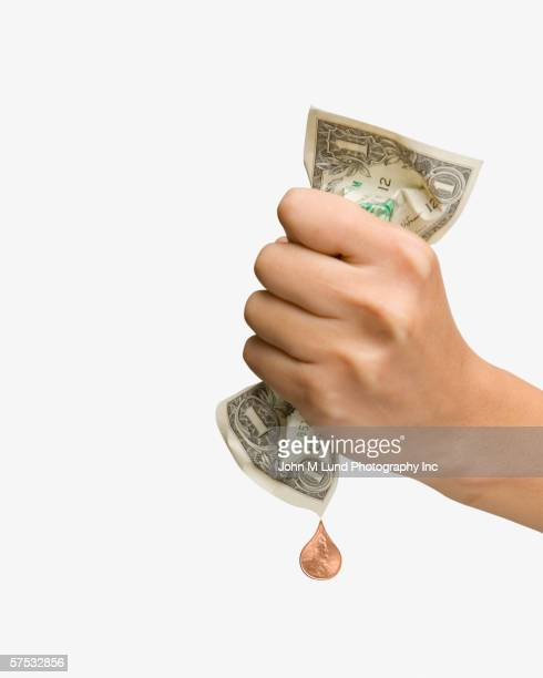 Woman squeezing a penny out of a dollar