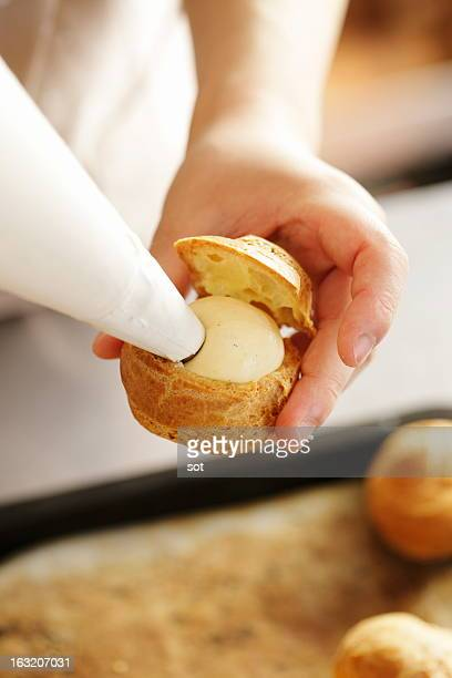 Woman squeezing custard cream into Cream Puff