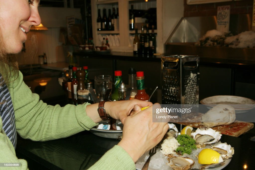 Woman squeezing lemon on oysters at Rodney's Oyster House, Yaletown. : Stock Photo