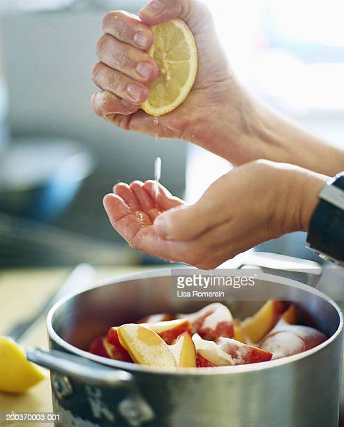 Woman squeezing lemon over pot of peaches