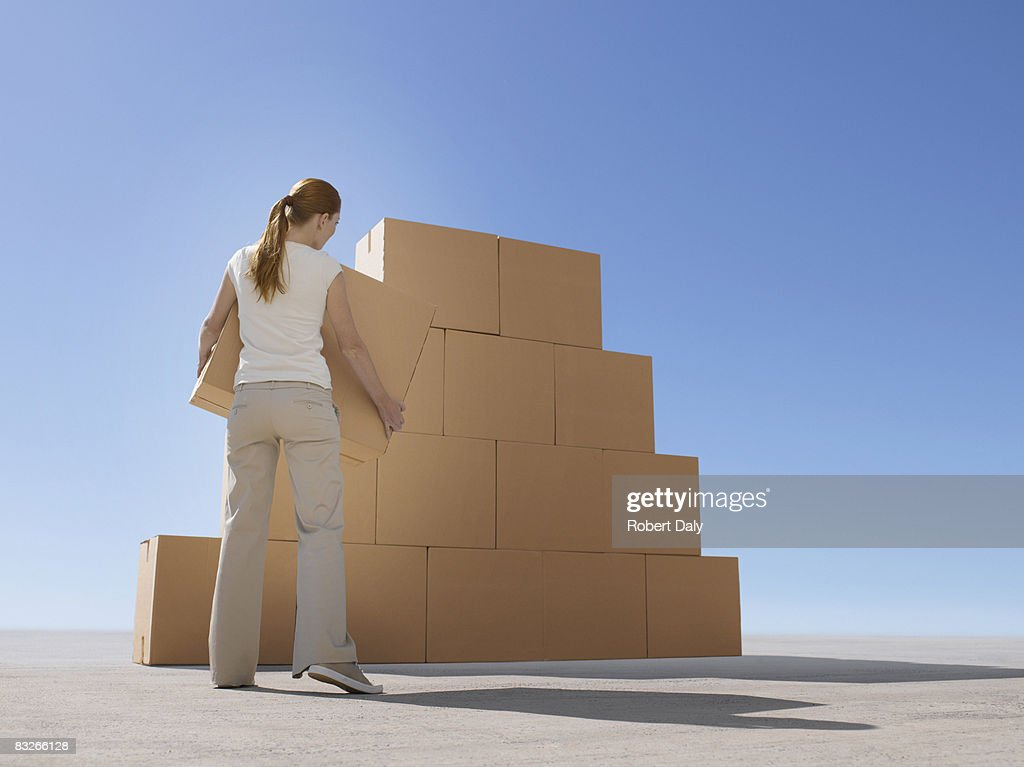Woman stacking boxes in desert : Stock Photo