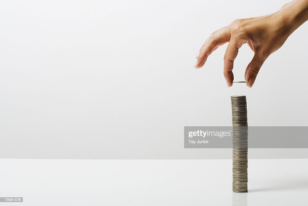 Woman stacking coins : Stock Photo