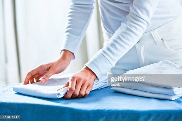 Woman Stacking Ironed Folded Shirts