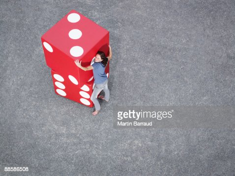 Woman stacking pair of giant dice : Stock Photo