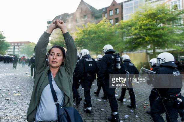 A woman stand between the police in Hamburg Germany on July 6 2017 The police stopped the leftradical demonstration quotG20 Welcome to Hellquot and...