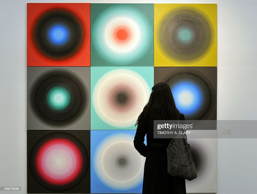 A Woman stand in front of art by Yan Lei titled 'Color wheel' during the press preview at the 2013 Armory Show one of the world's top art events...
