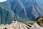One woman stand on mountain cliff with hands up