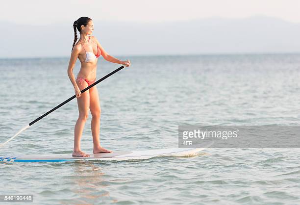 Woman Stand Up Paddling (SUP) at sunset