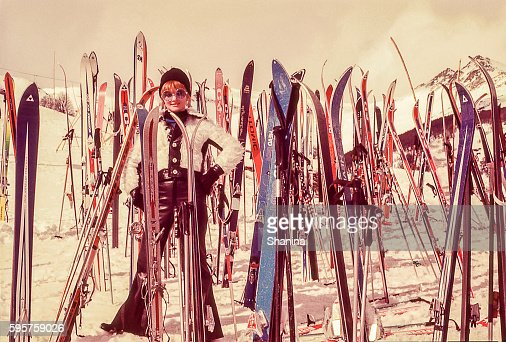 woman standind sorrounded by skis : Photo
