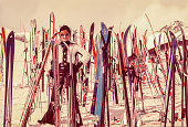 Vintage photo featuring a woman standing surrounded by skis on the snow.
