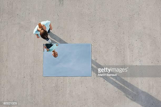 Mulher de pé acima de espelhos e a reflexão ao ar livre