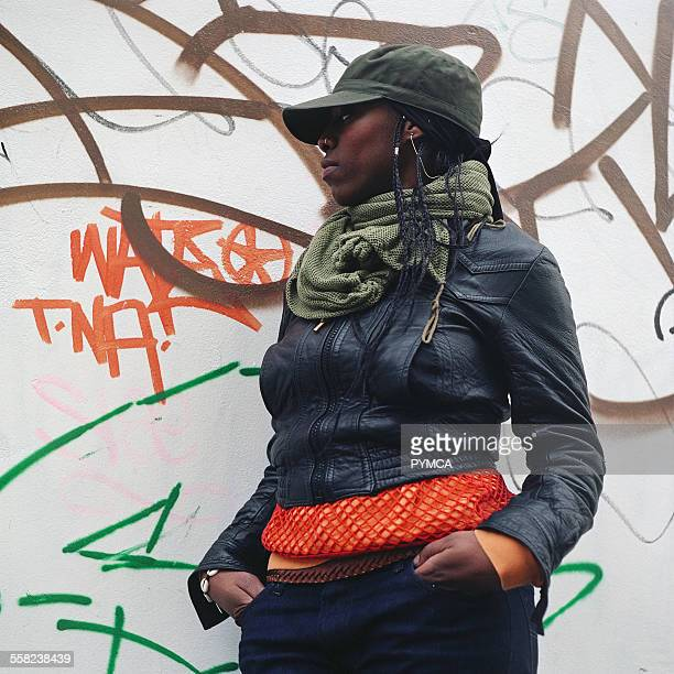Woman standing against a wall of graffiti Notting Hill London 2002