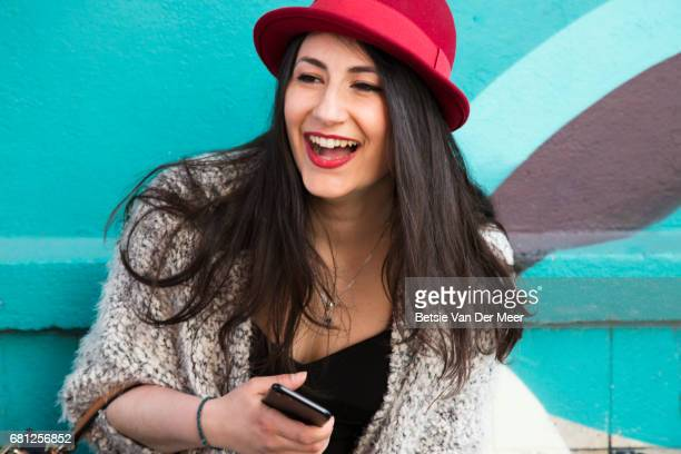 Woman standing against colourful wall, laughing.