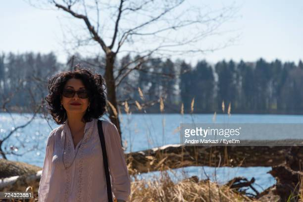 Woman Standing Against Lake On Sunny Day