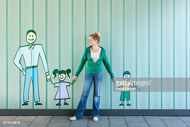 Woman standing against wall, finding her place between painted family members