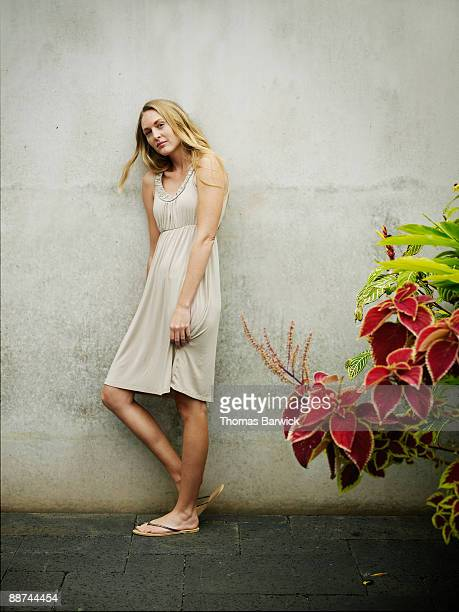 Woman standing against wall wearing sundress