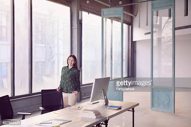 Woman standing alone in large modern bright design office