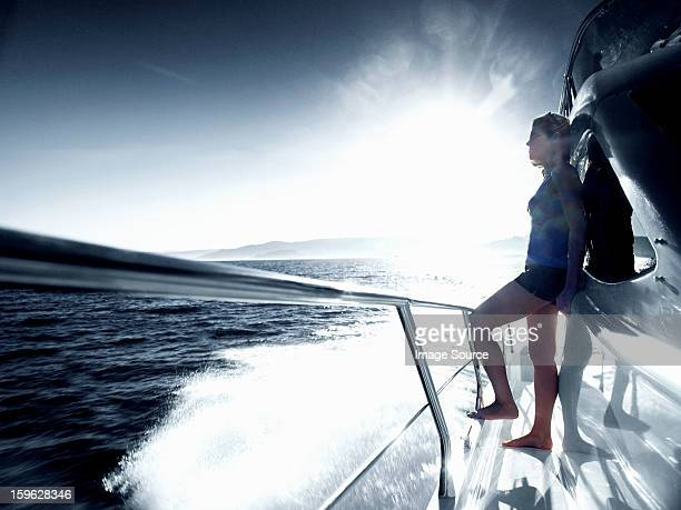 Woman standing alone on deck of yacht