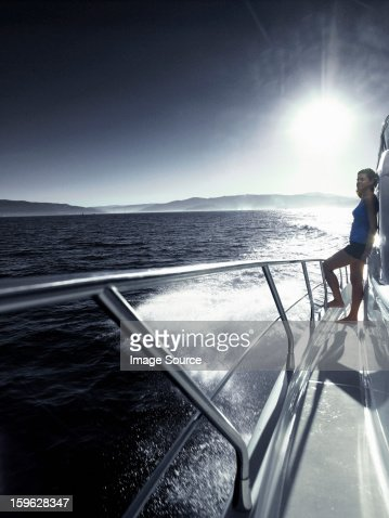 Woman standing alone on deck of yacht : Stock Photo