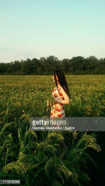 Woman Standing Amidst Rice Field Against Sky