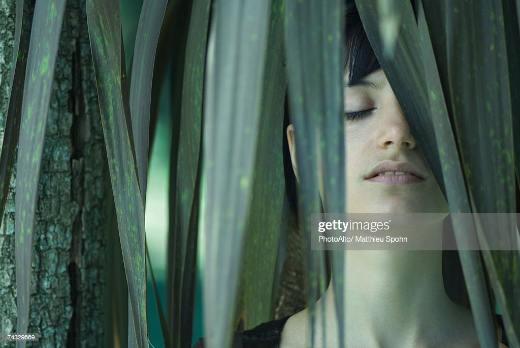 Woman standing among palm leaves, eyes closed : Stock Photo