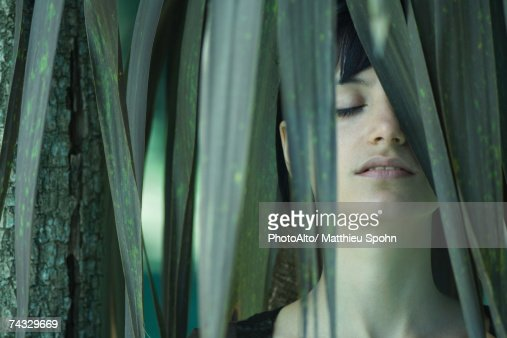 Woman standing among palm leaves, eyes closed : Foto de stock