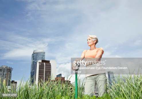 woman standing amongst greenery in city