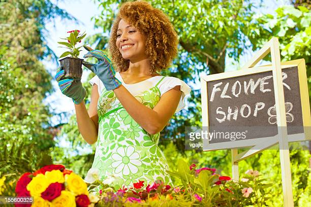 Woman Standing and cleaning plants outside florist.