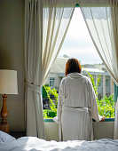 Woman standing and looking out of bedroom's window