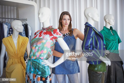 Woman standing and posing with mannequins : Stock Photo