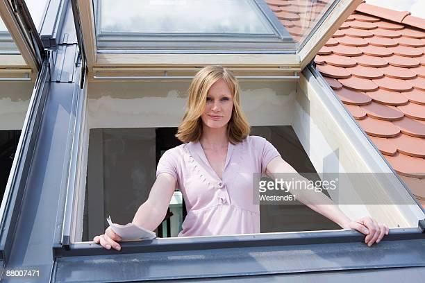 Woman standing at dormer window, portrait