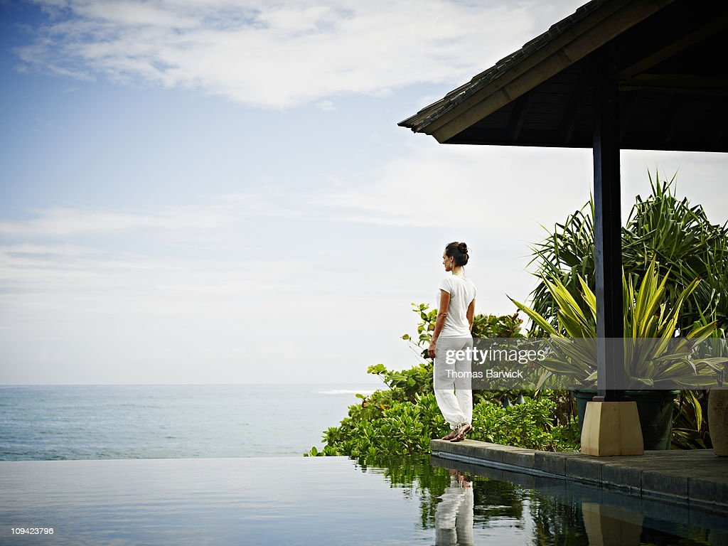 Woman standing at edge of infinity pool : Stock Photo