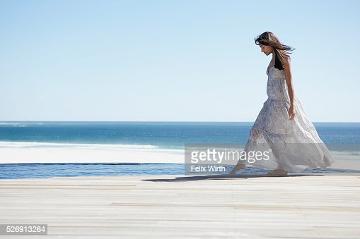 Woman standing at edge of pool : Stock Photo