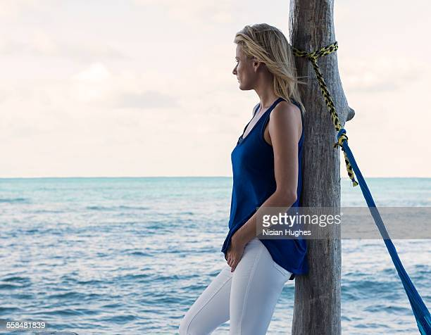 Woman standing at end of pier leaning on pole