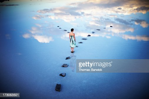 Woman standing at fork in stone pathway in lake
