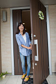 A woman standing at her front door.