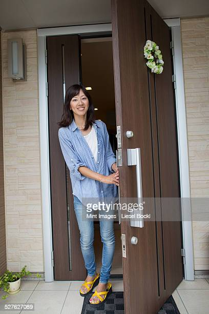 A woman standing at her front door.