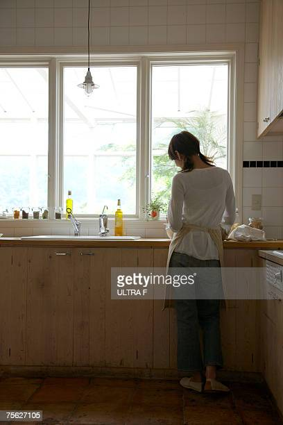 Woman standing at kitchen sink, rear view