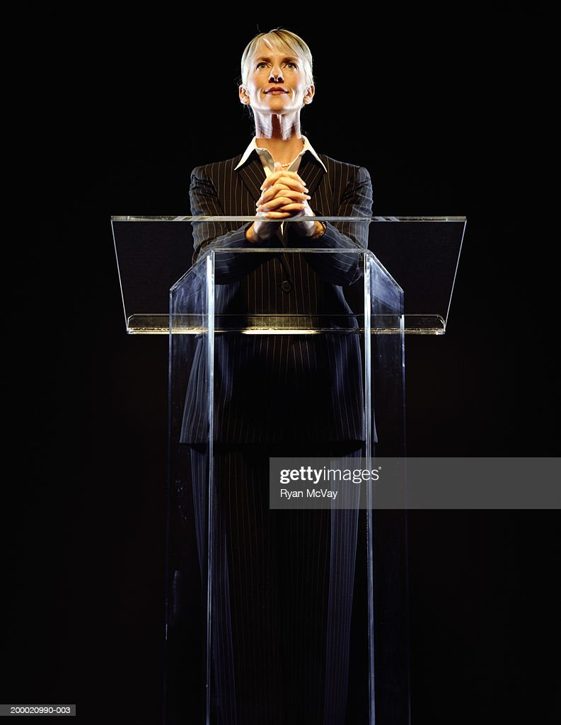 Woman standing at podium, hands clasped, low angle view : Stock Photo