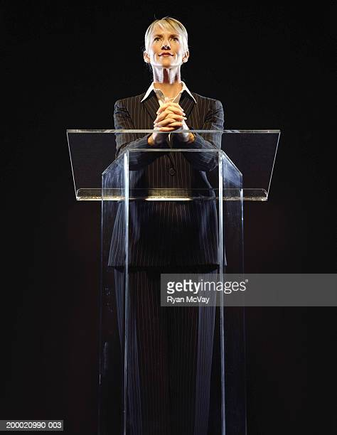 Woman standing at podium, hands clasped, low angle view