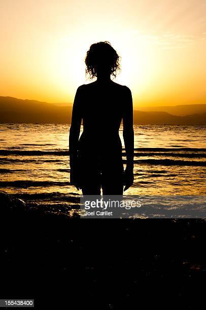 横に立つ女性の死海の日の出