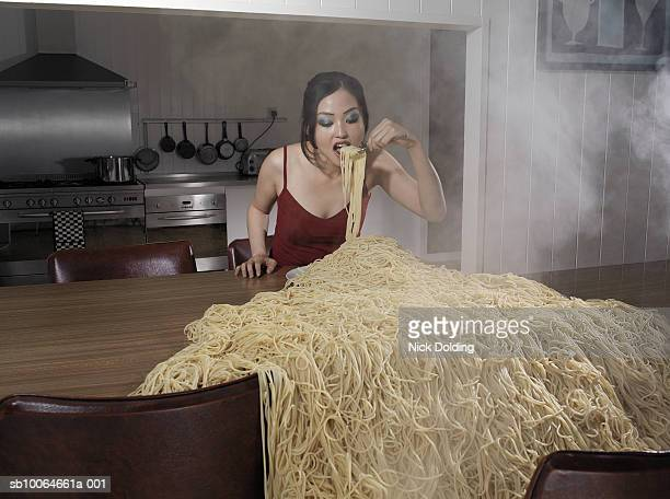 Woman standing at table eating heap of spaghetti