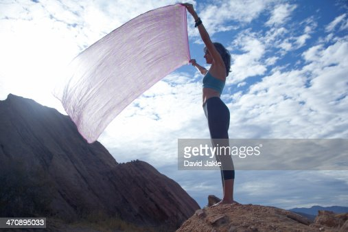 Woman standing at Vazquez Rocks holding sheet up : Stock Photo