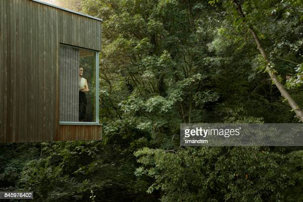 Woman standing at window in modern house watching the forest