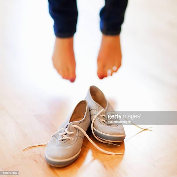 Frau mit nackten Fuß vor Canvas-Schuh