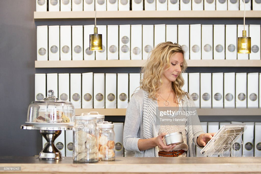 Woman standing behind counter : Stock Photo