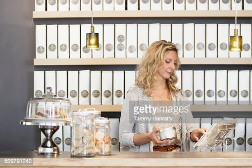 Woman standing behind counter : Stockfoto