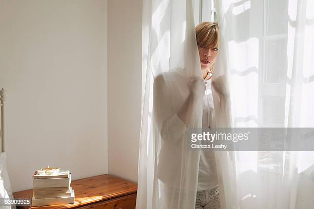 Woman standing behind curtain