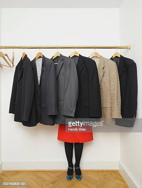 Woman standing behind suit jackets on hangers, low section